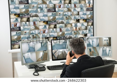 Security System Operator Looking At Cctv Footage While Talking On Telephone - stock photo