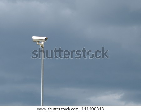 Security video surveillance camera on stormy sky background - stock photo