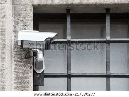 Security with a video surveillance camera at a jailhouse window - stock photo