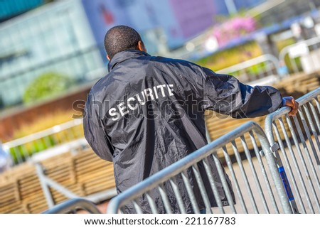 Security worker leaning over metallic fence and watching over the construction area - stock photo