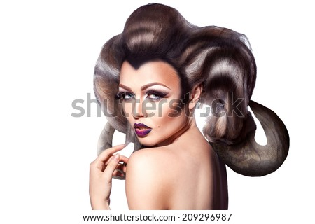 Seductive adult young female with creative horns in hairstyle looking at camera on white background - stock photo