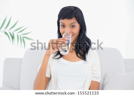 Seductive black haired woman in white clothes drinking water in a living room - stock photo