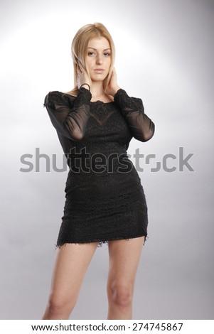 Seductive blond in creative black dress - stock photo