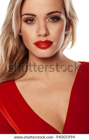 Seductive blonde woman with red lipstick wearing a matching red dress. - stock photo