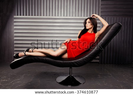 Seductive brunette lying on leather chair in red short dress - stock photo