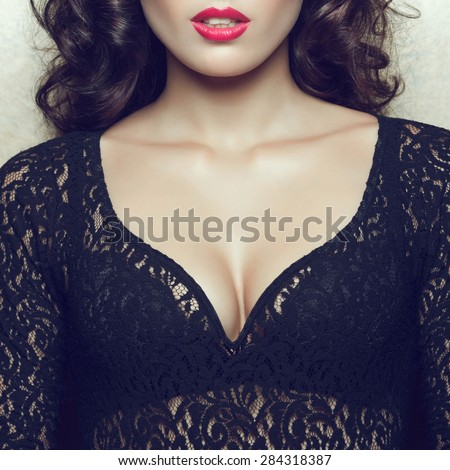 Seductive decollete concept. Portrait of beautiful brunette. Natural hairstyle, perfect make-up. Black lace cocktail dress. Healthy hair. Close up. Studio shot - stock photo