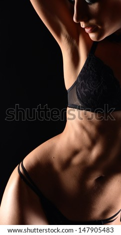 Seductive girl in lingerie on dark background - stock photo