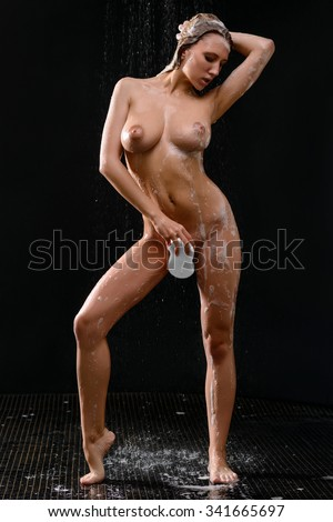 Seductive lady. Full length of seductive voluptuous magnetic girl holding sponge  and feeling content while  taking a shower - stock photo