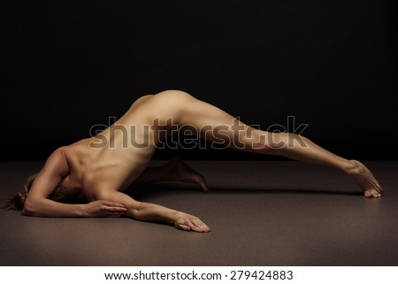 Seductive nude dancer posing in dark studio. Sports concept of athletic body. - stock photo