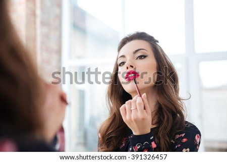 Seductive pretty young woman using lip brush for applying red lipstick to her lips looking in mirror - stock photo