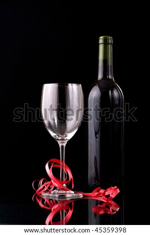 Seductive Valentines day setup with a bottle of red wine and a glass wrapped in red ribbon - stock photo