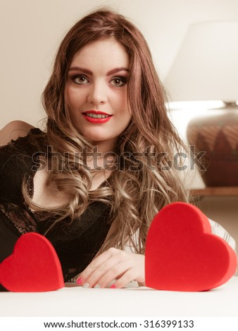 Seductive woman wearing lingerie in bed at home. Attractive sensual young girl with red heart shape boxes. Female underwear fashion. Valentines day love. - stock photo