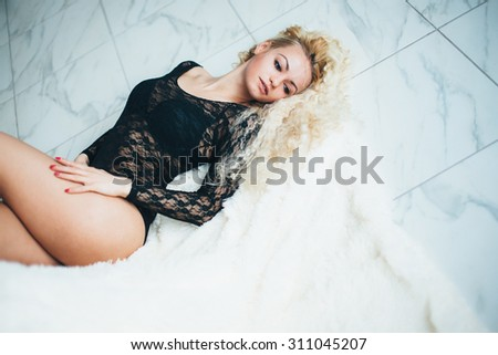 Seductive young girl in underwear lying on the floor. curly blonde - stock photo