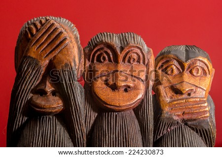 See hear speak no evil carved wooden monkeys on red background facing front - stock photo