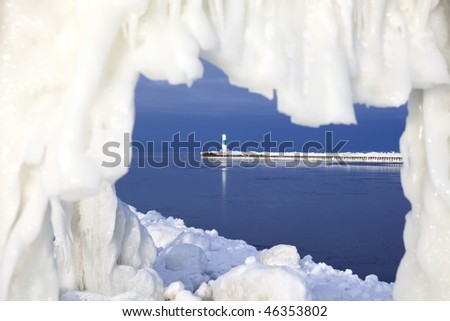 See the lighthouse in Grand Haven in Michigan though an ice hole - stock photo