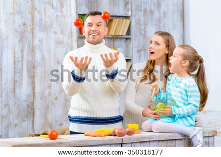 See  what I can. Pleasant loving father juggling the tomatoes and having fun with his family in the kitchen - stock photo