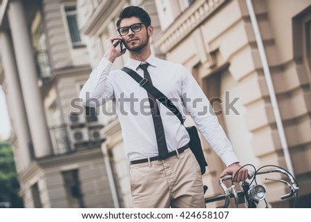 See you in office! Confident young man in glasses talking on mobile phone and holding hand on his bicycle while standing outdoors  - stock photo