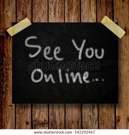 See you online on message note with wooden background - stock photo
