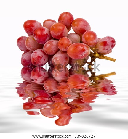 seedless red grape on isolated background with water reflection - stock photo