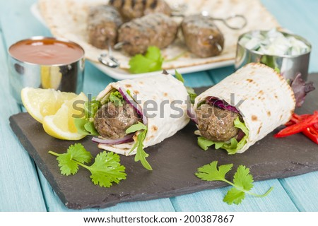 Seekh Kebab Wrap - Grilled spiced lamb mince and salad wrapped in a flatbread, served with chili sauce, lemon wedges and sliced chilies. - stock photo