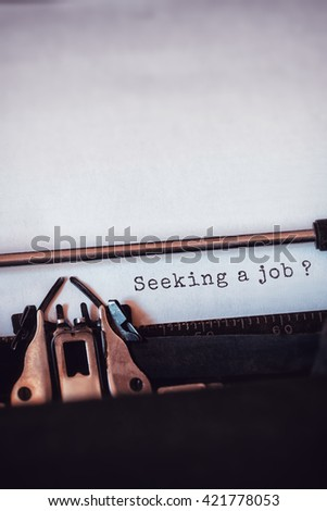 Seeking a job message on a white background against close-up of typewriter - stock photo