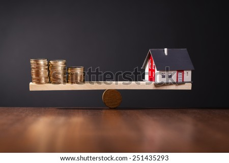 Seesaw with a house on one side and stacks of coins on the other side. - stock photo