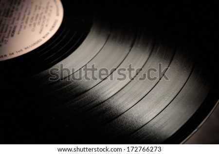 Segment of vinyl record with label showing the texture of the grooves, retro look  - stock photo