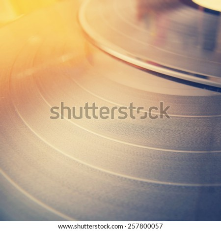 Segment of vinyl record with label showing the texture of the grooves, retro look, lifestyle style of photography, music background - stock photo