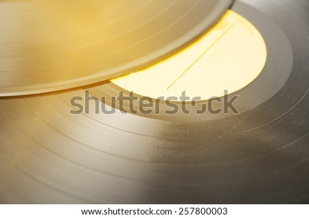 Segment of vinyl record with label showing the texture of the grooves, retro look, music background - stock photo