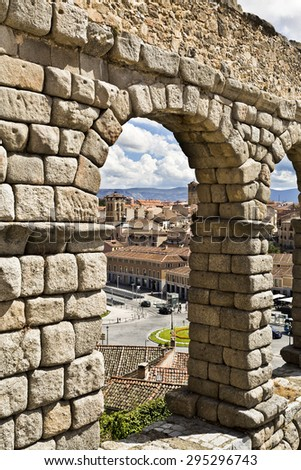 SEGOVIA, SPAIN - SEPTEMBER 14, 2014: View of the old town through an arch of the roman aqueduct in Segovia, Spain - stock photo