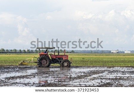 SELANGOR, MALAYSIA - JANUARY 31, 2016: Worker uses a machine to tilling the soil for planting rice on paddy field in Sekinchan, Malaysia. Sekinchan is one of the major rice supplier in Malaysia. - stock photo