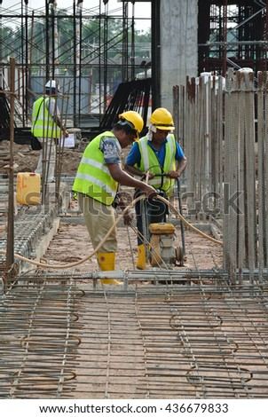 SELANGOR, MALAYSIA -NOVEMBER 25, 2015: Construction workers using soil compactor machine to compact soil at the construction site. - stock photo