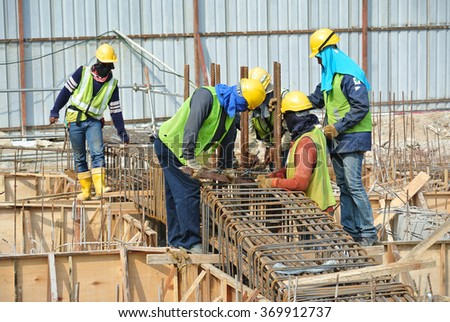 SELANGOR, MALAYSIA   SEPTEMBER 22, 2015: Construction workers fabricating ground beam reinforcement bar at construction site in Selangor, Malaysia on September 22, 2015.  - stock photo