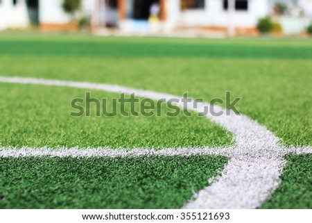 selected focus at white line on green synthetic grass indoor soccer field with blur building behind - stock photo