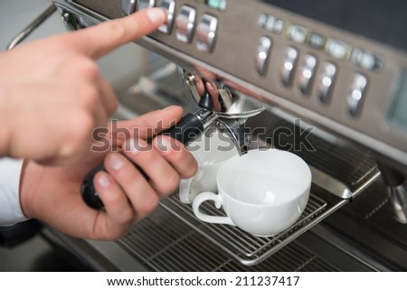 Selected focus on the hands of professional barista pushing the button and holding the handle of the coffee machine - stock photo