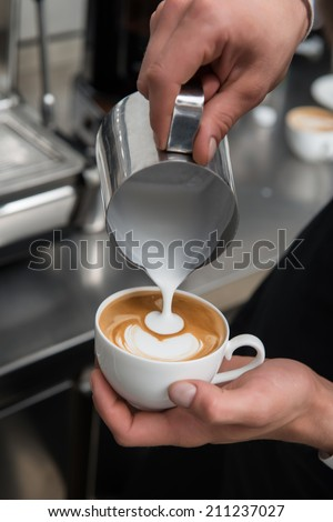Selected focus on the professional barista pouring milk into the cup of coffee making a pattern - stock photo