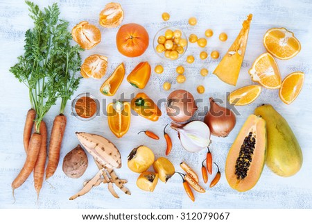 Selection of assorted fresh orange toned vegetables and fruit raw produce on white rustic background, pumpkin butternut carrot papaya pawpaw capsicum pepper sweet potato cherry tomatoes chilli orange - stock photo