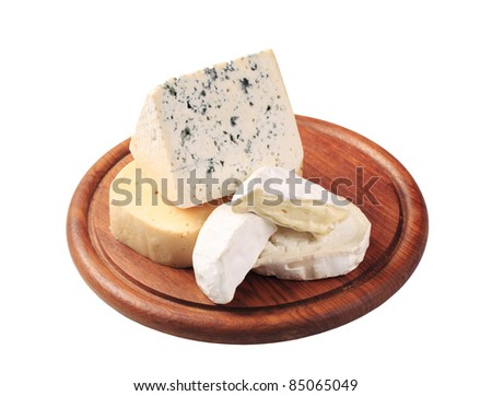 Selection of cheeses on a cutting board - stock photo