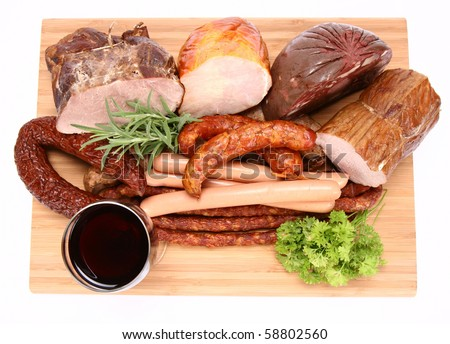Selection of cold meat (ham, sirloin, headcheese, sausages, hot dogs) decorated with rosemary and parsley and a glass of red wine on a chopping board - stock photo