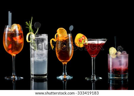 Selection of colorful Cocktails with garnish from tall to low isolated on black background - stock photo