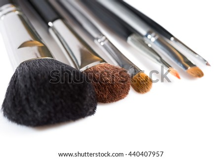 Selection of different makeup brushes for applying a range of cosmetics displayed with the bristles towards the camera over white in a close up view in a beauty and glamour concept - stock photo