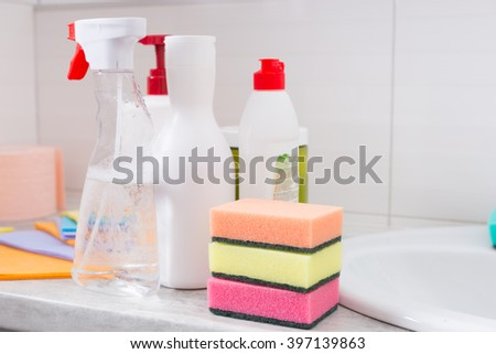 Selection of domestic cleaning products in a bathroom with three colorful sponge scourers spray bottles and cloths - stock photo
