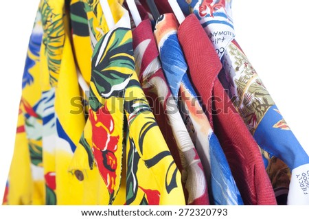 Selection of five colorful yellow, red, blue and green Hawaiian shirts arranged on hangers on white background - stock photo