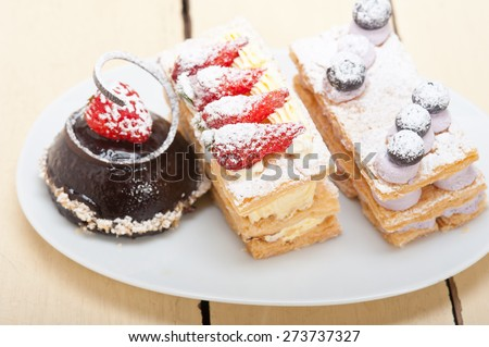 selection of fresh cream napoleon and chocolate mousse cake dessert plate  - stock photo
