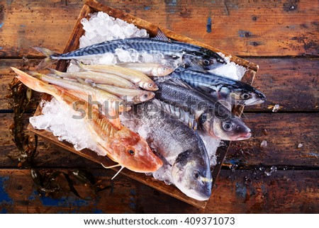 Selection of freshly caught marine fish for the table in a wooden crate of crushed ice on an old wooden table, viewed from above - stock photo