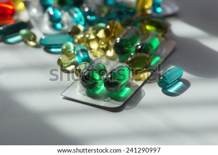 Selection of multi-colored gelatin capsules on sunlit table. - stock photo