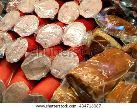 Selection of packed salami on display for sale in a shop - stock photo