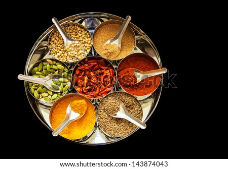 Selection of spices with spoons arranged in a tin with black background - stock photo