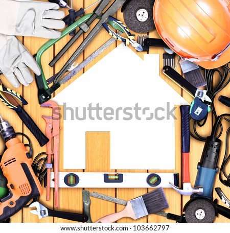 Selection of tools in the shape of a house on old wood - stock photo