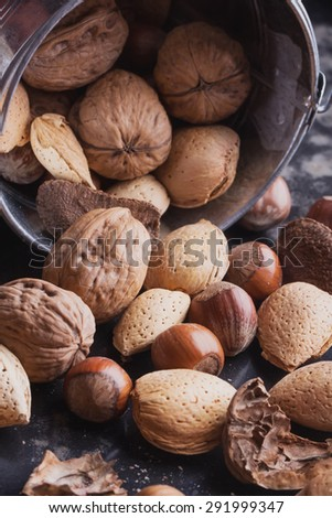 Selection of various nuts: almonds, Brazilian, walnuts in the tiny vintage bucket, black background - stock photo